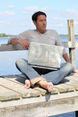 man-on-laptop-by-a-lake